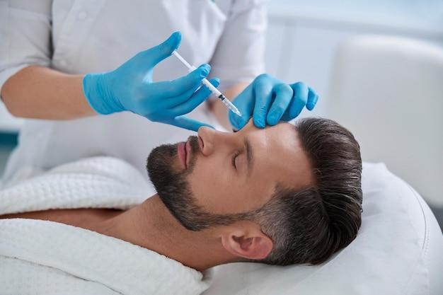 Schoonheidsspecialiste in blauwe handschoenen doet injectie bij wenkbrauwliftprocedure om de patiënt in de kliniek te laten rijpen