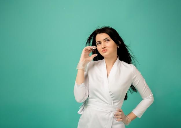 Schoonheidsspecialiste in een wit medisch pak houdt een medicijn op turkoois