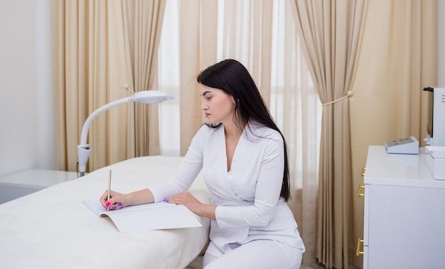 Schoonheidsspecialiste in een wit uniform zit bij de bank en schrijft in een notitieboekje op kantoor