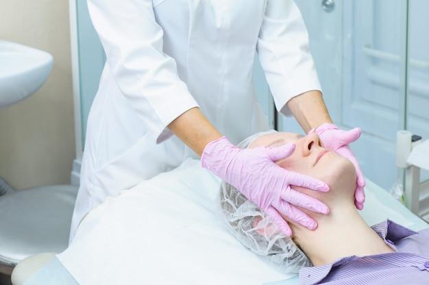 Schoonheidsspecialiste in roze handschoenen past peeling op het gezicht van de vrouw. cosmetische procedure voor verjonging en reiniging van de huid. spa behandeling