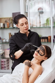 Schoonheidsspecialiste in zwarte handschoenen koolstofmasker toe te passen op mooie vrouwelijke klant in spa, cosmetologie en beauty concept