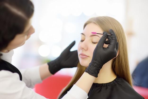 Schoonheidsspecialiste kamt wenkbrauwen met behulp van een speciale borstel op het jonge mooie model gezicht. gezichtsverzorging en make-up
