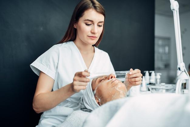 Schoonheidsspecialiste maakt gezichtsmasker voor jonge vrouw