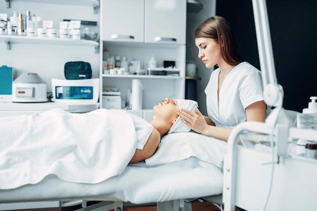Schoonheidsspecialiste maakt gezichtsmassage aan vrouwelijke patiënt