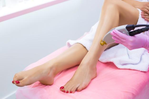Schoonheidsspecialiste maakt laser ontharing op de mooie en slanke benen van een meisje in een kliniek.
