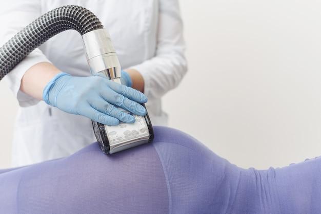 Schoonheidsspecialiste maakt lpg-massage van de buit van een jonge vrouw in een paars pak.
