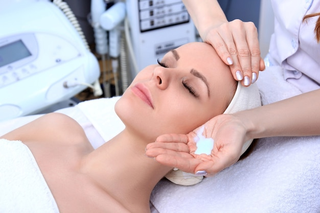 Schoonheidsspecialiste maakt reinigende en exfoliërende gezichtsbehandeling voor mooie meiden. schoonheidssalon.