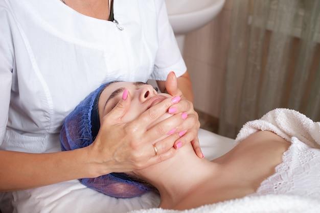 Schoonheidsspecialiste masseert het gezicht van de cliënt
