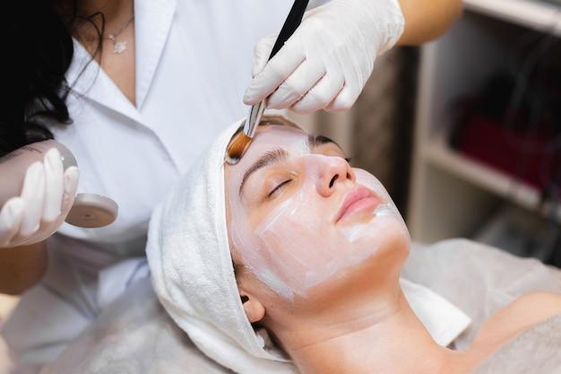 Schoonheidsspecialiste met een borstel past een wit vochtinbrengend masker toe op het gezicht van een jonge meisjescliënt in een spa-schoonheidssalon