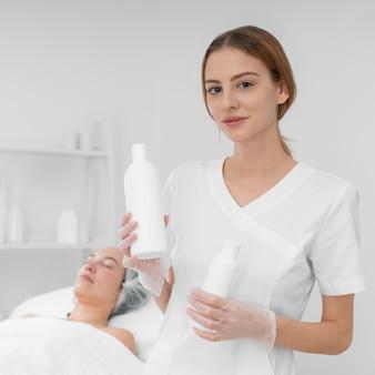 Schoonheidsspecialiste met lotion voor vrouwelijke cliënt
