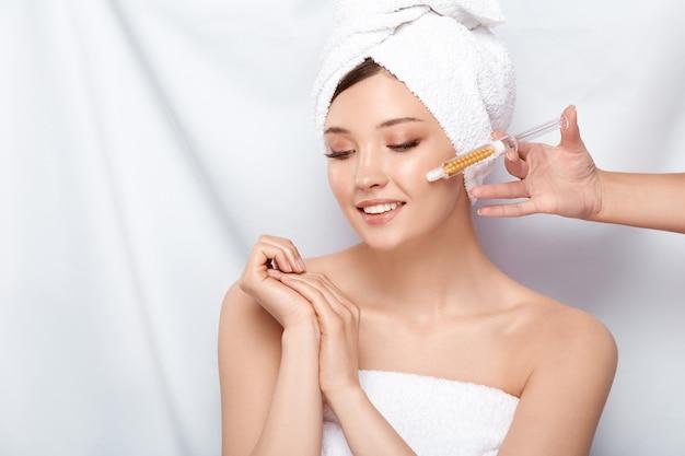 Schoonheidsspecialiste met spuit in de buurt van het gezicht van de vrouw in badhanddoek en open schouders