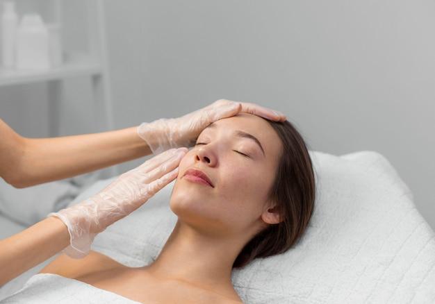 Schoonheidsspecialiste met vrouwelijke cliënt bij salon voor routine van de gezichtsverzorging