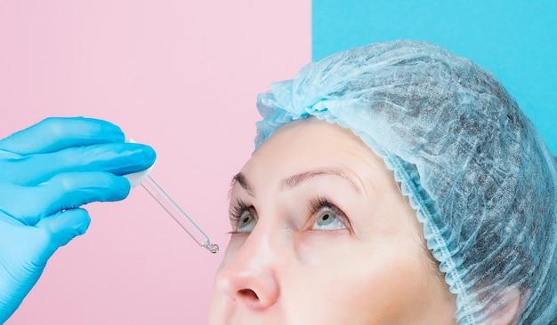 Schoonheidsspecialiste past een cosmetisch product toe onder de ogen, oogarts druipt ogen naar vrouw in kliniek.