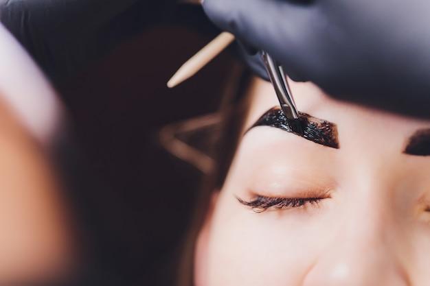 Schoonheidsspecialiste past henna verf op getrimde wenkbrauwen in een schoonheidssalon