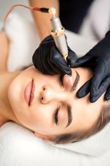 Schoonheidsspecialiste permanente make-up toe te passen op de wenkbrauwen van een jonge vrouw door speciale tatoeage werktuigmachine