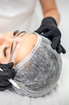 Schoonheidsspecialiste permanente make-up toe te passen op wenkbrauwen door tattoo-werktuigmachine