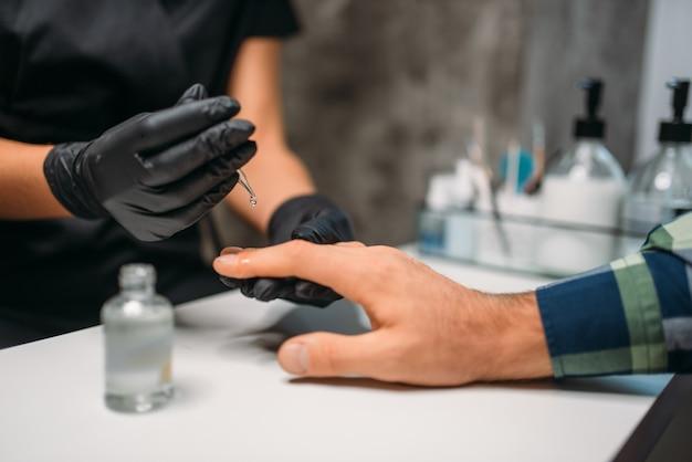 Schoonheidsspecialiste polijsten nagels aan mannelijke cliënt in salon