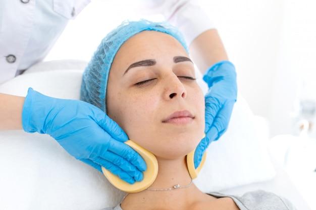 Schoonheidsspecialiste reinigt het gezicht van de patiënt met sponzen voordat het masker wordt aangebracht voor huidverzorging