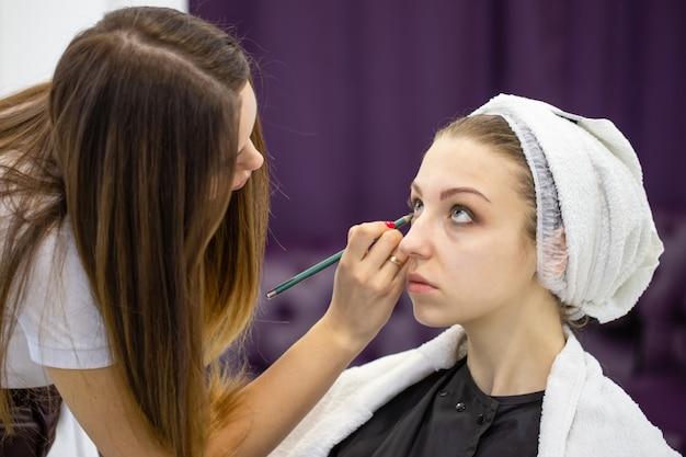 Schoonheidsspecialiste schildert ogen met een cosmetisch potlood aan een jong mooi meisje