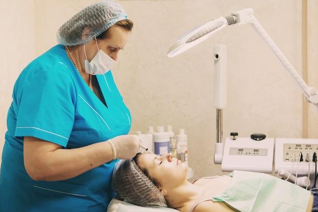 Schoonheidsspecialiste voert een naaldmesotherapiebehandeling uit op het gezicht van een vrouw