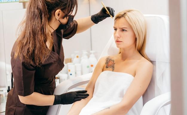 Schoonheidsspecialiste vrouw voert de correctie van wenkbrauwen uit op mooie modellen in cosmetische kast