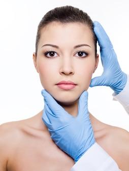 Schoonheidsspecialiste wat betreft het gezicht van de aantrekkelijke gezondheidsvrouw. plastische chirurgie. geïsoleerd op wit
