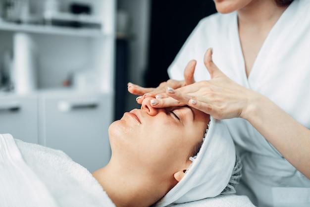 Schoonheidsspecialiste wrijft de crème op het gezicht van de vrouwelijke patiënt