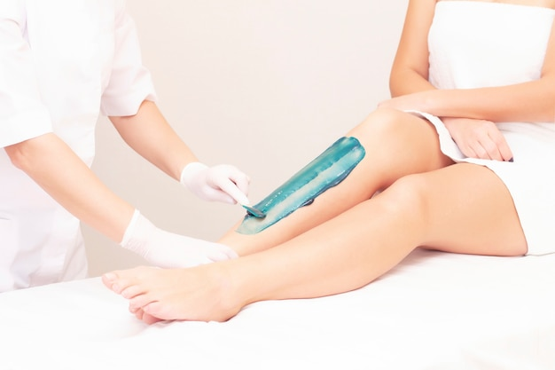 Schoonheidsspecialiste zet azuleen op de benen van het meisje