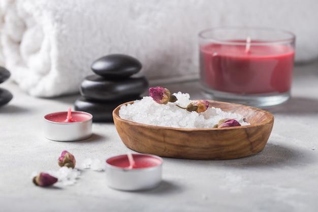 Schoonheidsstilleven van de fles van de massageolie aroma essentieel en natuurlijk geurzout met stenen, kaarsen op concrete grijze lijst. samenstelling van spabehandeling