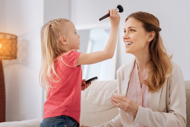 Schoonheidstijd. vrolijk aangenaam gelukkig meisje houdt een make-upborstel en kijkt naar haar moeder terwijl ze plezier met haar heeft