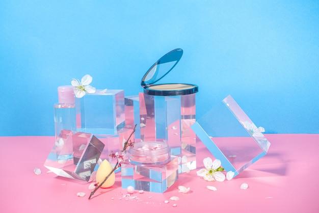 Schoonheidsverzorging, make-up cosmetica op podia van transparante glazen sokkels, mock-up op een felroze blauwe achtergrond met lente-sakura-kersenbloemen