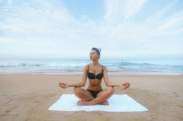 Schoonheidsvrouw beoefent yoga en mediteert in de lotuspositie op het strand. meditatie. actieve levensstijl. gezond en yogaconcept. fitness en sport Premium Foto