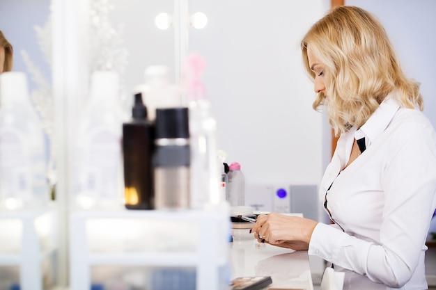 Schoonheidsvrouw die make-up toepassen. mooi meisje dat in de spiegel kijkt en schoonheidsmiddel met een grote borstel toepast