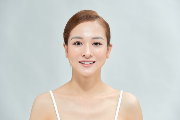 Schoonheidsvrouw met charmante glimlach aan u met geïsoleerde blauwe achtergrond, aziatisch