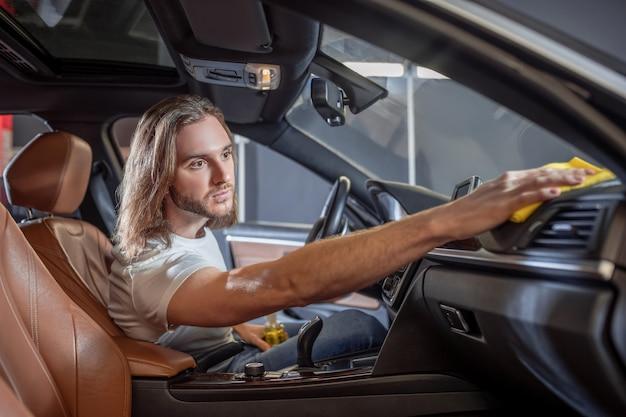 Schoonmaak, auto. aantrekkelijke energieke jonge volwassen man afvegen van oppervlakken in auto-interieur in goed humeur