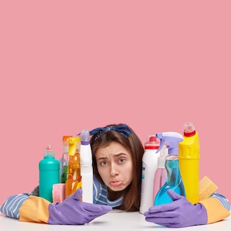 Schoonmaak concept. boos vrouw portemonnees onderlip, draagt beschermende handschoenen, vormt in de buurt van multi gekleurde flessen met schoonmaakmiddelen