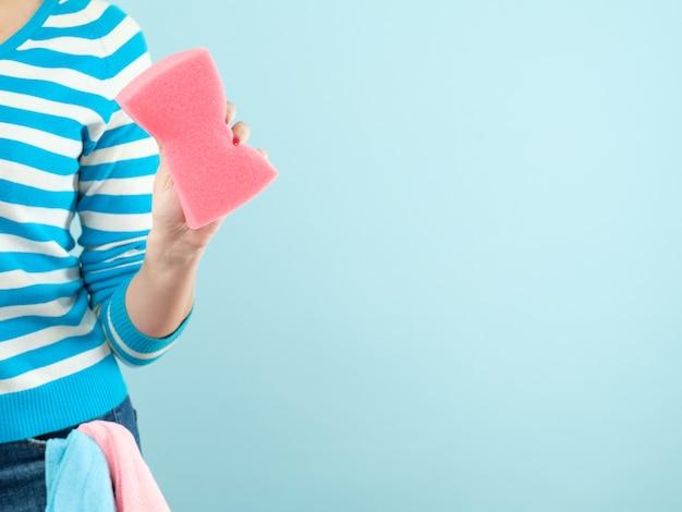 Schoonmaak concept. diy thuis opruimen. vrouw met spons en doeken in zak. kopieer ruimte op blauwe muur.