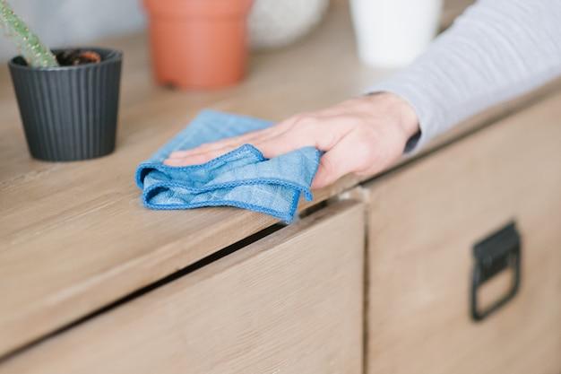 Schoonmaak concept. ochtend huishoudelijke taken. mans hand afstoffen dressoir.