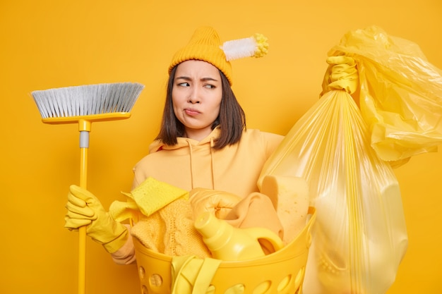 Schoonmaak dienstverleningsconcept. ontevreden aziatische vrouw kijkt naar polyethyleen zak vol afval houdt bezem brengt huis in orde doet huishoudelijk werk draagt casual kleding geïsoleerd over gele achtergrond