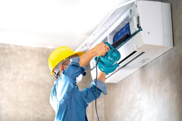 Schoonmaak en onderhoud airco aan de muur met blazer in slaapkamer of kantoorruimte.