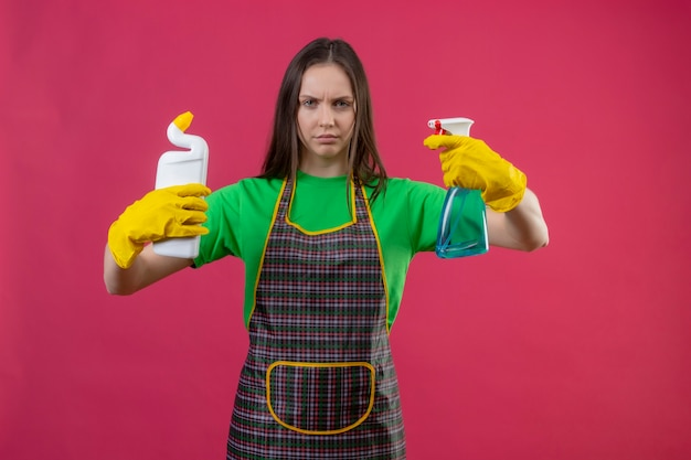 Schoonmaak jonge vrouw dragen uniform in handschoenen met schoonmaakmiddel en spray op geïsoleerde roze muur