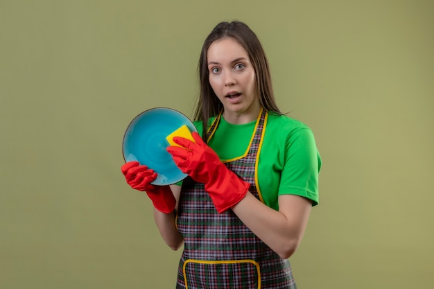 Schoonmaak jonge vrouw uniform dragen in rode handschoenen afwas op geïsoleerde groene muur