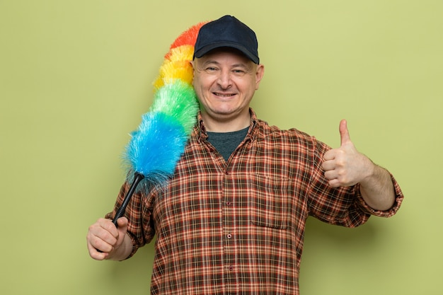 Schoonmaak man in geruit hemd en pet met kleurrijke stofdoek kijkend naar camera glimlachend vrolijk duimen opdagen staande over groene achtergrond