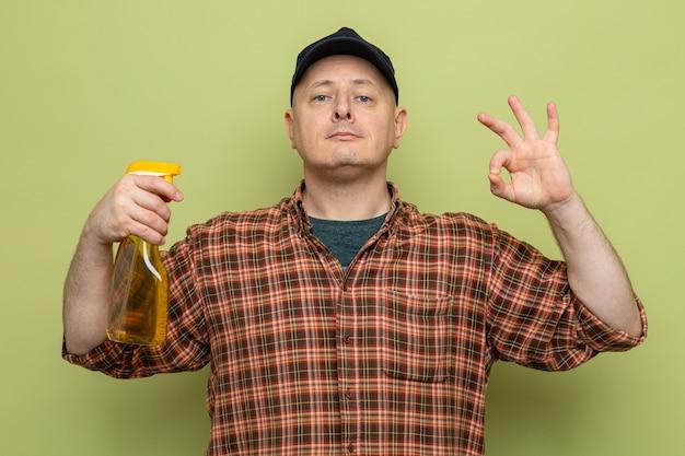 Schoonmaak man in geruit hemd en pet met schoonmaakspray in de hand kijkend naar camera met ok teken met zelfverzekerde uitdrukking die over groene achtergrond staat