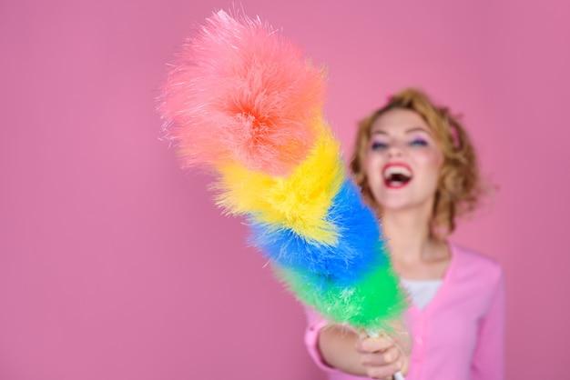 Schoonmaak pin-up vrouw glimlachend pinup meisje houdt kleurrijke stofdoek borstel schoonmaak service pinup girl