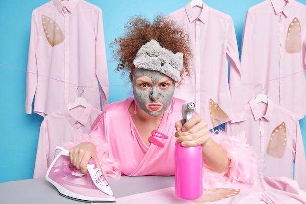 Schoonmaak service hygiëne en huishoudelijk werk concept. scrupuleuze vrouw met krullend haar ziet er geïrriteerd uit en past een kleimasker op het gezicht vast met schoonmaakmiddelsprays in de kamer die bezig zijn met het strijken van kleding