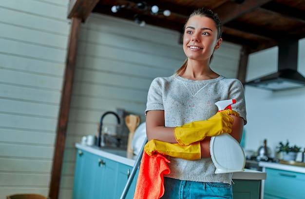 Schoonmaakconcept. een aantrekkelijke vrouw in vrijetijdskleding en beschermende handschoenen met een doek en spray in haar handen staat op het punt om algemene schoonmaak in de keuken te doen.