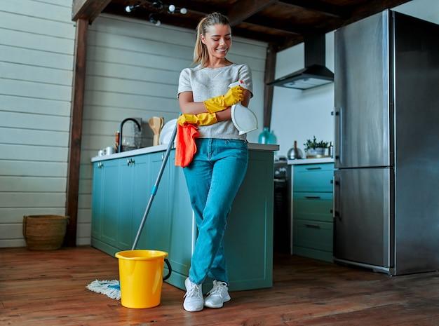 Schoonmaakconcept. een aantrekkelijke vrouw in vrijetijdskleding en beschermende handschoenen met een vod en spray in haar handen, een dweil en een emmer in de buurt van haar gaan de algemene schoonmaak in de keuken doen.