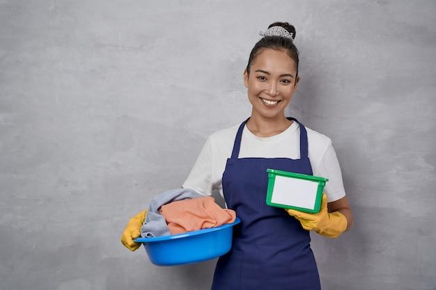 Schoonmaakdag. portret van een gelukkige huisvrouw of meid in uniform met bekken vol vuile kleren en groene plastic doos met wascapsules, staande tegen een grijze muur. huishouden, huishoudelijk werk