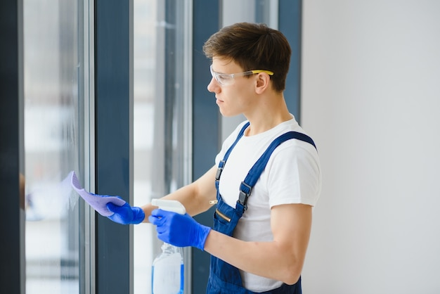 Schoonmaakdienst kwam om nieuw huis schoon te maken. hardwerkende man zorgvuldig schoon venster. zijaanzicht